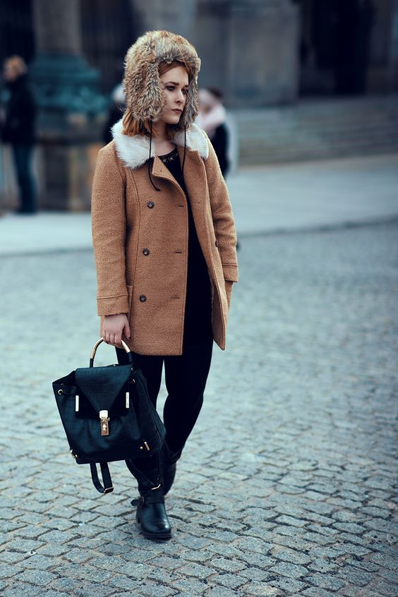 Influencer and fashion blogger babe Christina Key is wearing a cozy winter jacket in brown and a black dress