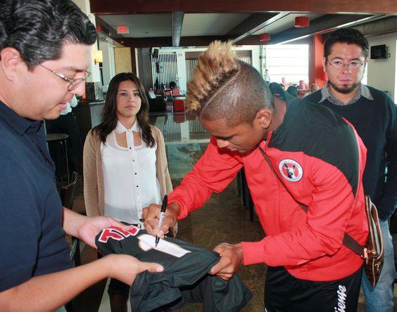 Fidel Martinez firmando el jersey de visita 2013 de Xolos