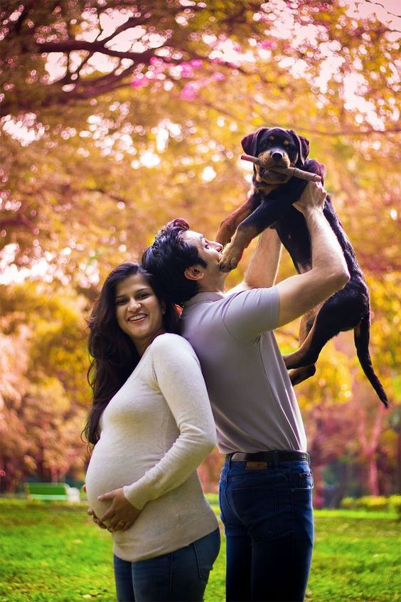 They were asked to get rid of their pet dogs by people around them, Family and Friends. They shot back with this amazing photo shoot. | Husband with the dog standing facing opposite side in frame with his expecting wife | Outdoor Maternity Photoshoot Ideas | Indian Maternity Photoshoot Ideas | Adorable maternity photo shoot ideas with pets for cute pictures | Cute Pregnancy Photoshoot with Dogs for expecting couples | Function Mania