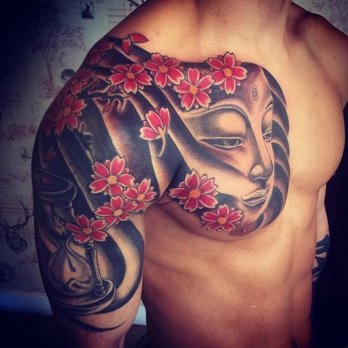 Japanese Cherry Blossom Tattoo With The Face Of A Buddha And Hourglass Blossom Tattoo Cherry Blossom Tattoo Tattoos For Guys