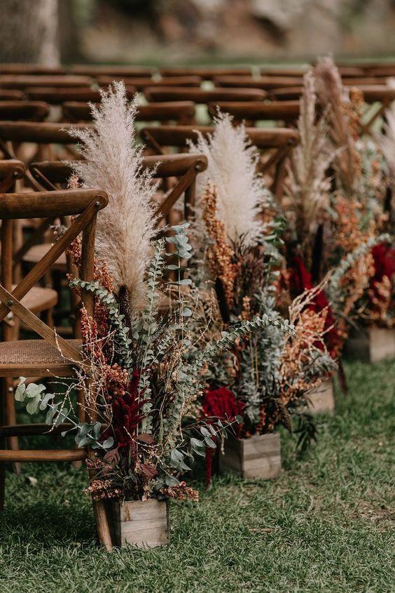 Bei der Boho Hochzeit im Freien wird der Weg zur Trauung mit Pampasgras, Trockenblumen und Greenery dekoriert, die in kleinen Vintage Holzkistchen stecken. #bohohochzeit #bohohochzeitimfreien #hochzeitsdekoboho #hochzeitsdekotrauung #hochzeitsdekogreenery #hochzeitsdekopampasgras #hochzeitsdekotrockenblumen