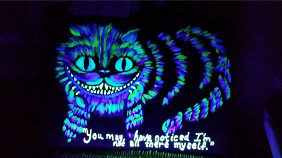 Glowing Cheshire cat created with acrylic, neon & glow in the dark paints on foam board.