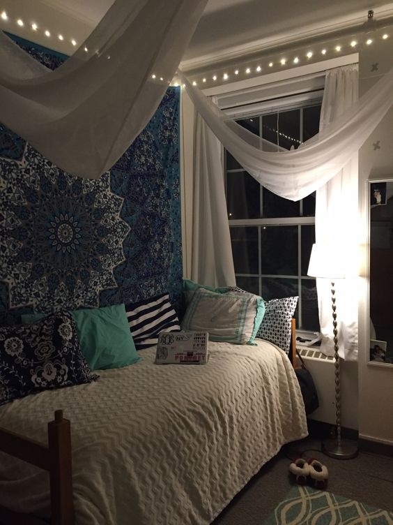 Boho Chic Dorm with beautiful wall tapestry, colorful pillows, white sheers draped from the ceiling, white curtains and bed spread keep the room from feeling too dark with the large wall tapestry, lights around the top of the ceiling, free standing lamp, area rug