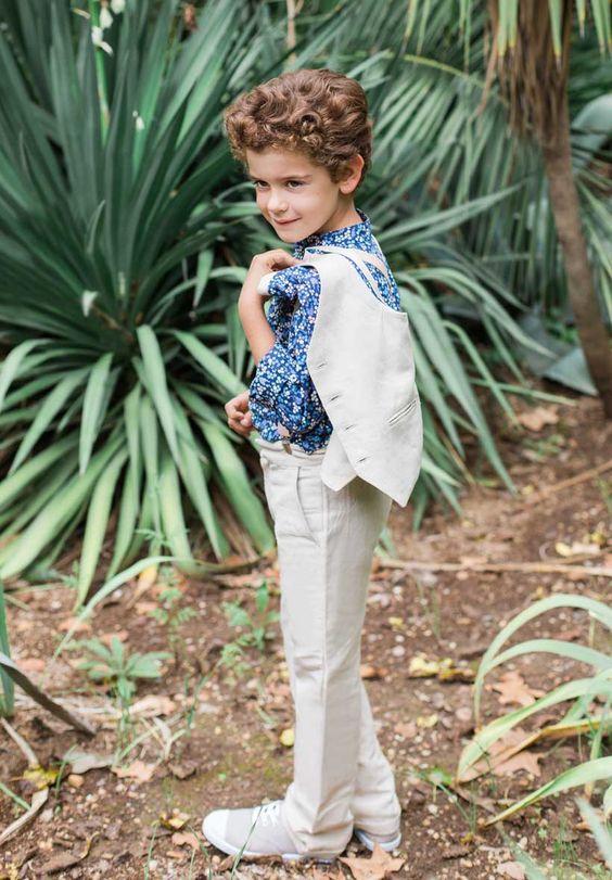 Ce garçon d'honneur porte notre ensemble en lin : avec la chemise Émile en imprimé floral Daisy bleu marine, la veste Lucien, ainsi que le pantalon Léon.