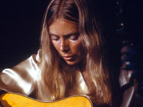 Joni playing guitar.