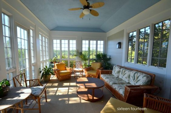 Warmth And Cozy Sunroom Design Examples To Inspire You : Good Looking Screened Front Porch Sunroom Decoration With Blue Wall Paint Color And Ceiling Fan Also Oval Coffee Table And White Windows Frames Along With