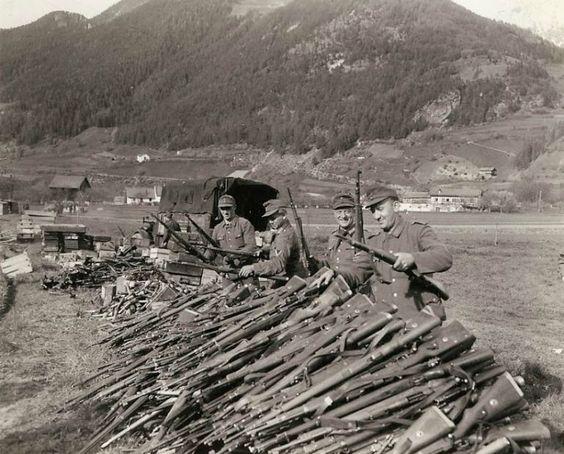 """""""End of the Line"""" General Palmer comentó.  La rendición de la 19a Ejército.  ¡El fin!  Con la capitulación final de Alemania a los aliados, los soldados alemanes que tienen armas de calibre de más de cinco años en contra de casi toda Europa y los EE.UU., renuncien a sus rifles a sus conquistadores estadounidenses cerca de Landeck, Austria.  Parecen felices de que todo ha terminado.  Granadas de mano y otros equipos se pueden parecen amontonados más allá de los fusiles."""