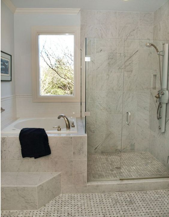 Small bathroom with a tiny bathtub and adjacent shower unit