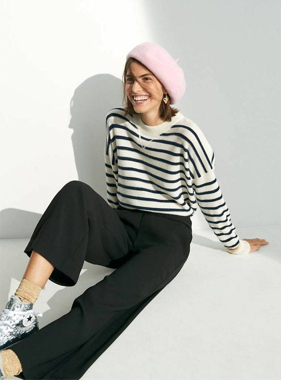 pink beret, striped sweater, wide-leg pants, and sequin sneakers.