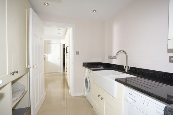 Cream to match the kitchen, with a huge double butler sink, laundry appliances and a cat bed on the left!