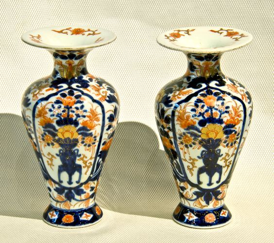 """Pair of small porcelain hand decorated Imari palace shaped vases.  The body of each piece has a panel on either side depicting a vase on a low table holding an arrangement of flowers.  The decoration is in underglaze blue, overpainted iron red and gold enamels. The flared rim is decorated in iron red and gold.  [7.25"""" h x 3.5"""" top dia.]  Japan, Meiji Period, c. 1880."""