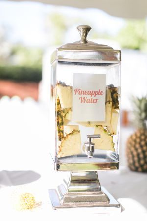 Yummy pineapple water for a Hawaiian destination wedding: http://www.stylemepretty.com/destination-weddings/2015/08/26/tropical-colorful-wedding-in-kauai-botanical-garden/   Photography: Heather Cook Elliott - http://heathercookelliott.com/