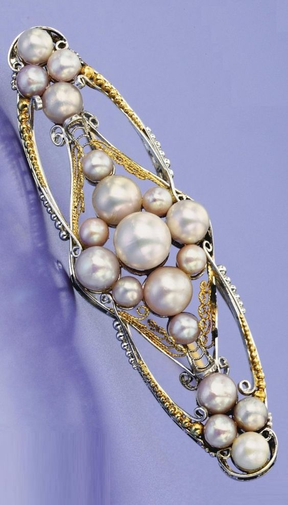 A vintage platinum, gold and pearl brooch, Tiffany & Co., designed by Louis Comfort Tiffany, circa 1920. The stylised oval plaque decorated with filigree and beadwork, set in the centre and at either end with clusters of 19 pearls in pastel hues, signed Tiffany & Co. #LouisComfortTiffany #vintage #brooch