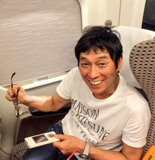 新幹線の座席に座って笑っている明石家さんまの画像・壁紙