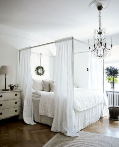 white romantic bedroom.  ikea four poster bed, swedish chest, white bedding, wreath.