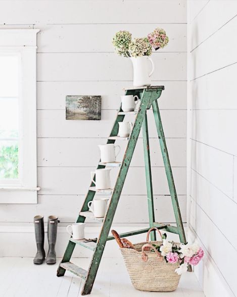 A vintage green painted ladder with ironstone, a French market basket, and galoshes #farmhousestyle #shiplap #pastels