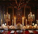 The dining table is decorated with gilt candelabra and set with Meissen's Blue Onion porcelain