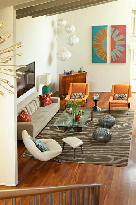 Old meets new as a series of 1960s-style lights cascade over an Aromic Age bar and turquoise lamps from the 1950s flank a midcentury-inspired custom sofa designed by interior designer Gillian Lefkowitz.