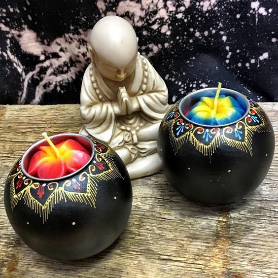 Buddha Statues & Hand painted wood mango tea light. All black mango wood tea light holder comes with candle and hand painted accents. Candle/accent colors may vary.