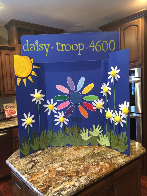 Cookie Booth Sign - each girl made a daisy and glided to board. Each girl traced and cut out their handprint for the grass. Each girl stamped their name on their handprint. Center flower is Girl Scout promise with all the petals. Fun group activity... Cookie sale!!