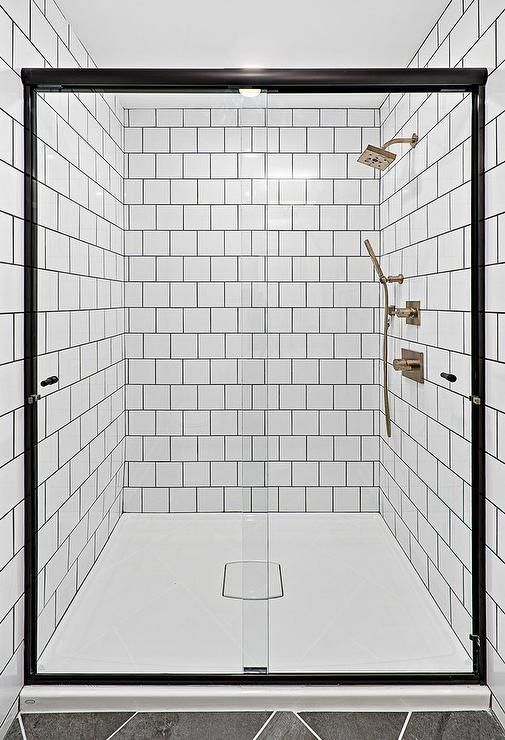 A Sliding Glass Shower Door Accented With A Black Steel Frame