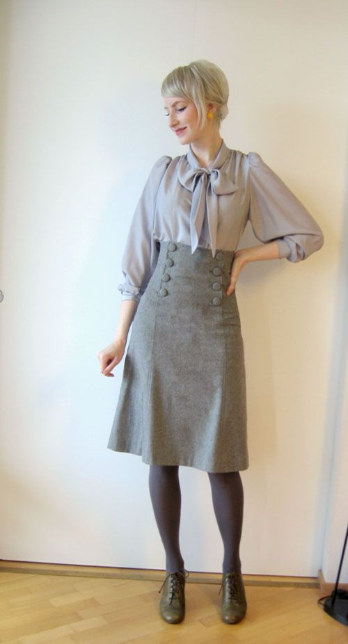 What a doll. - light grey satin 3/4 poet sleeve pussy bow blouse, waist high a line knee length medium grey tweed skirt with sailor buttons, dark grey tights, grey booties