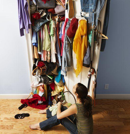 una mujer esta al lado de un clóset totalmente desordenado y lleno de ropa