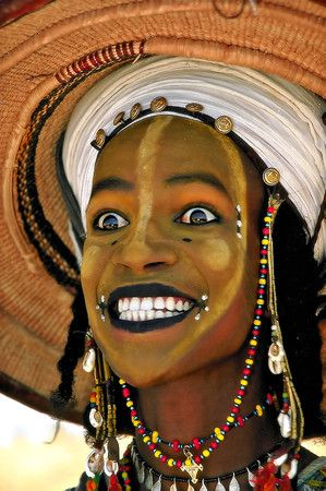 """The Wodaabe - A """"Yaake"""" Dancer. In preparation, the men spend hours applying make-up to highlight their facial gestures. A pale yellow powder applied to the entire face offers a beautiful and striking contrast to a man's otherwise dark skin. Kohl drawn around the eyes and lips draws attention to their white, gnashing teeth and rolling eyes during the dance. A painted white line, which starts at the forehead and ends at the chin, serves to elongate the nose."""