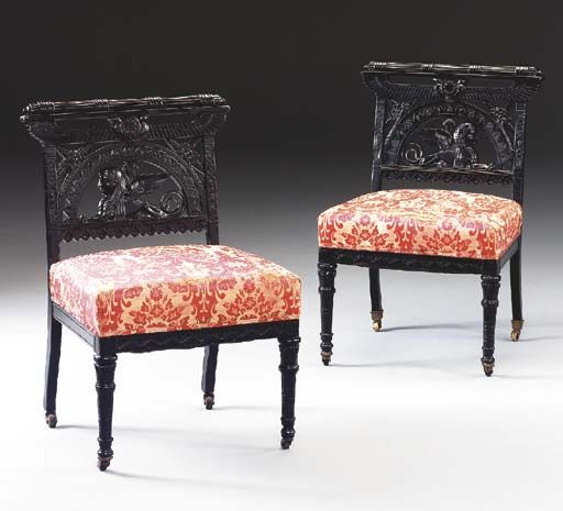 A PAIR OF EGYPTIAN REVIVAL CARVED AND EBONIZED SIDE CHAIRS New York, 1860-1880 The carved and reeded crestrail above a pierced back depicting a central sphinx within a pierced arch with floral carved corners below a central medallion flanked by incised stiles, over an overupholstered seat with incised geometric design on seatrail, on ring-turned and incised legs, fitted with castors 30¾in. high (2)