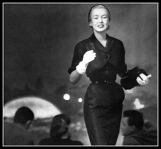 Catherine McManus (Mrs. William McManus) a fashion editor at Vogue, wears silk shantung sheath with short bolero jacket (the Hollywood Bowl in background), Vogue, May 15, 1951