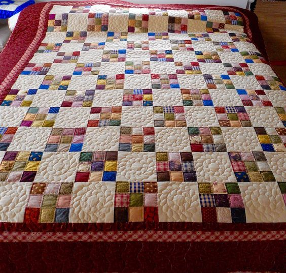Our Amish made Nine Patch Calico Quilt is full of surprising color, offset by spaces of heavily hand quilted neutral white squares. Gorgeous border, too!