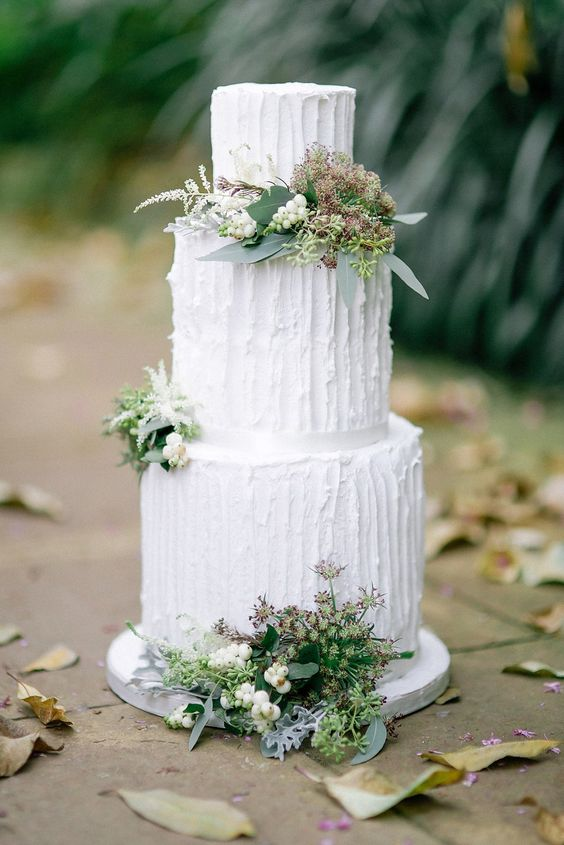 Three tier wedding cake decorated with wild flowers. Photography by http://jesspetrie.com/