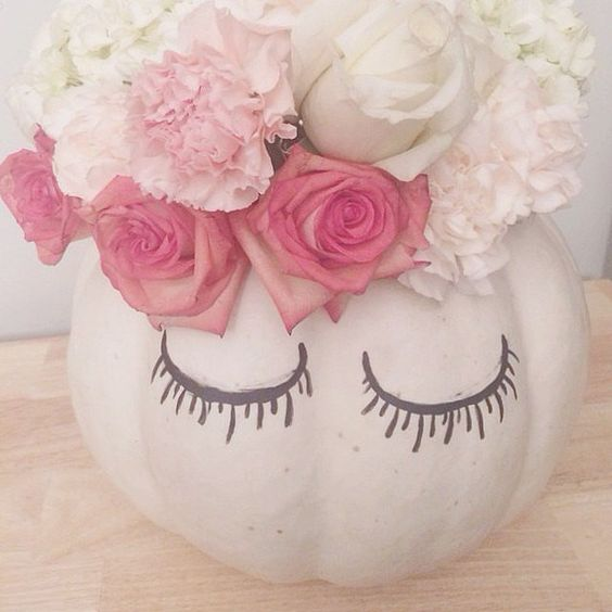 After hollowing out your pumpkin, fill the top with flowers and use a Sharpie to draw lashes on the front s...