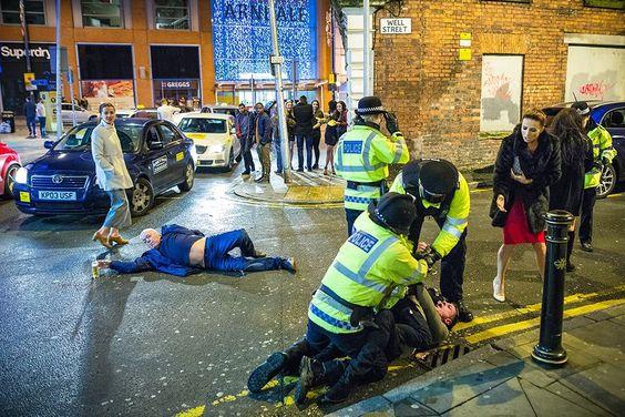 Un uomo steso a terra, nel mezzo della strada, avvicina la mano alla sua birra. Una donna, in pelliccia e abito rosso, si rivolge a un ragazzo che sta per