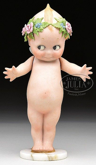 RARE KEWPIE WITH MOLDED FLORAL WREATH.