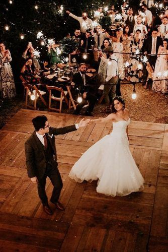 rustic backyard wedding decoration the bride and groom dance on a wooden dance floor in the rustic style in the courtyard of the waters with glowing lights fernando caballero via ins