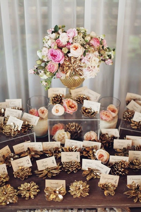 gold and pink escort card station/pinecones cut into sections and sprayed gold for card holders:
