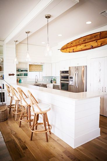 21 Homes That Prove Surf Is Chic // surfboards as decor // white kitchen, bamboo stools, glass pendants