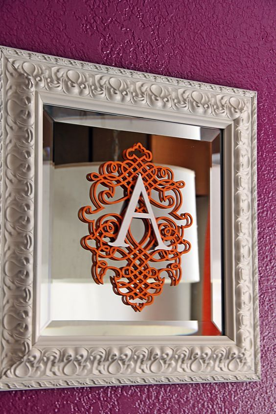 Framed beveled mirror. Laser cut wood design painted orange with wood letter mounted in center with tacky putty. Wood pieces bought at Michael's.