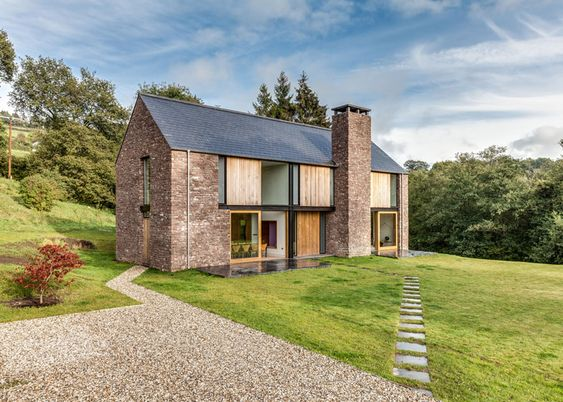 Contemporary Hall Wales Hall + Bednarczyk Architects paired sandstone with contemporary details for this rural house in Wales, designed to resemble local agricultural barns