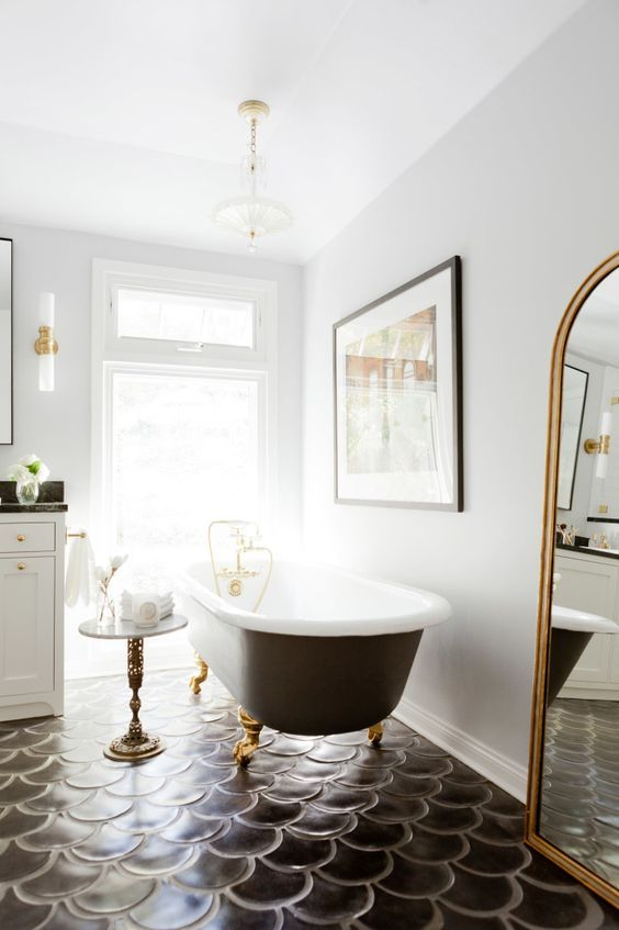 The gorgeous vintage clawfoot tub was a Craigslist find, which Rosa painted matte black on the outside and reglazed on the inside. It's a stunning find! And the Marc Royce piece above it adds even more luxury.
