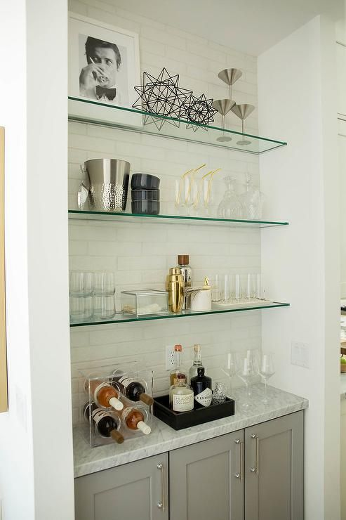Glass Shelves Are Fixed Against A White Brick Wall Accenting A Bar Nook Fitted With Gray Cabinets Fin In 2020 Glass Bar Shelves Glass Shelves Glass Shelves In Bathroom