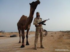 Matthew VanDyke with AK-47 and a camel in Sirte, Libya