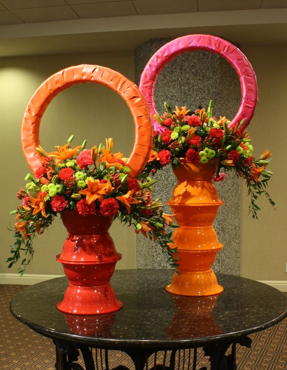 """VIVID PASSION""  Tom Kenison AIFD  Colorful Plastic bowls from the dollar store are stacked upon each other to make the pedestals which support the vividly colored crescent shaped arrangements.  Ribbon wrapped wreaths add personality and completes the composition"