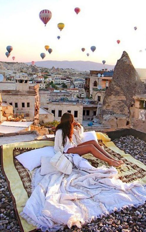 girl under sheets watching balloons over turkey