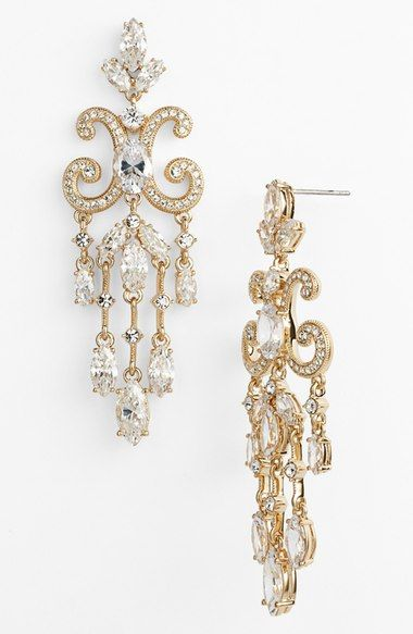 Embossed scrollwork suspends bevies of watery crystals from hand-polished statement earrings defined by seductive sparkle.
