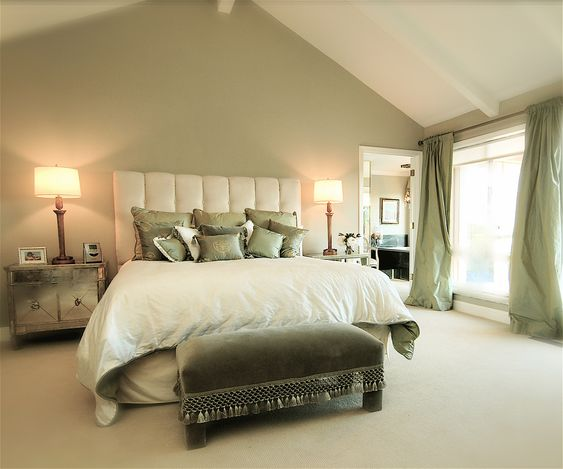 Sage green accent wall behind the all white bed, with green curtains