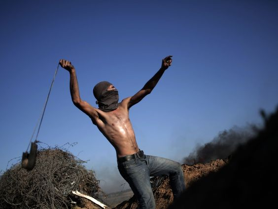 Palestinian protesters clash with Israeli soldiers on the Israeli border in Bureij, central Gaza.  Khalil Hamra, AP