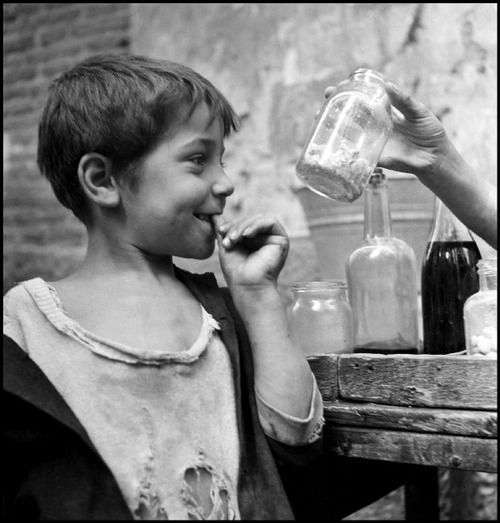 by David Seymour  Naples, 1948. The temptation of candy to a ragged urchin, one of thousands filling the dirty, narrow streets of Naples.