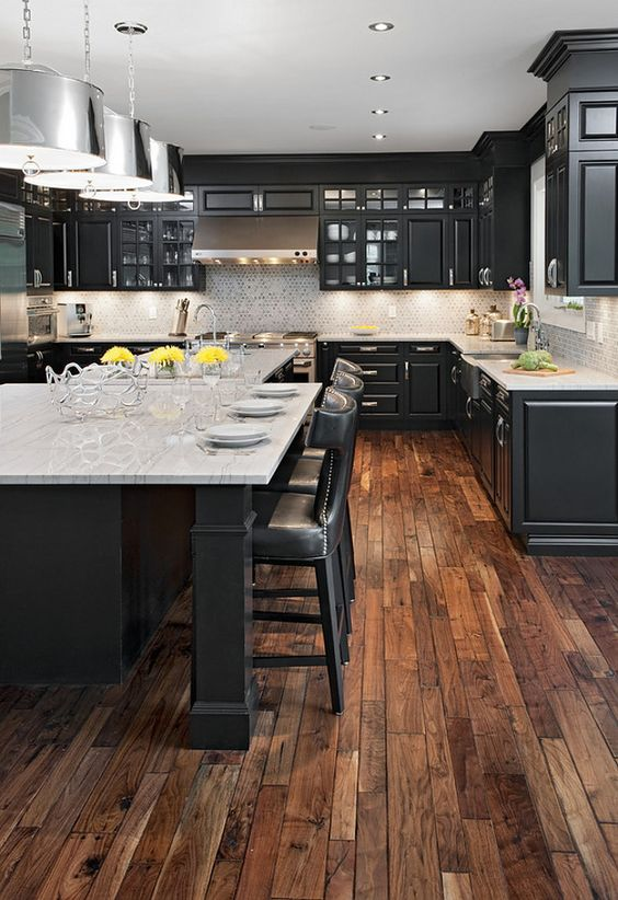 This kitchen tones things down a bit with the rustic style wood floors and basic cabinets. But the marble countertop and silver lights help to class things up a little more.